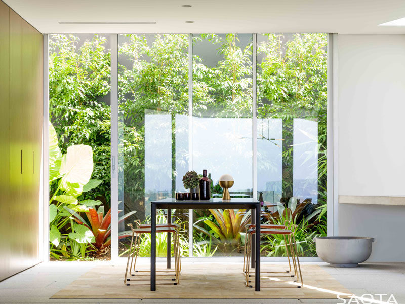 Floor-to-ceiling windows show off the landscaped garden in this dining room. #Windows #Landscaping