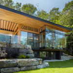 A Couple Of Contemporary Cottages Overlook A Lake In Canada
