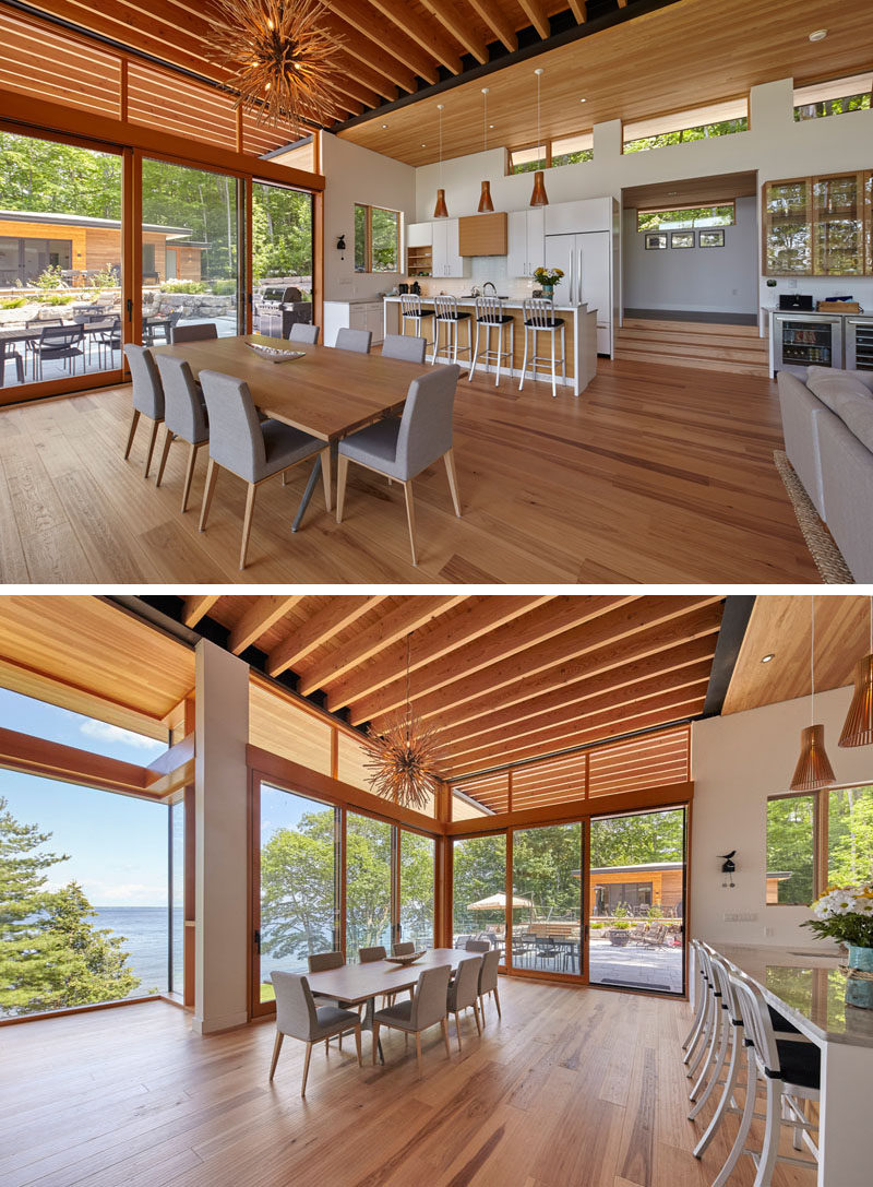 This modern cottage has large windows, an exposed ceiling, a white kitchen with an island, and a dining area that opens up to a landscaped area, creating and indoor/outdoor living environment. #CottageInterior #ModernInteriorDesign #Windows #WhiteKitchen #DiningRoom