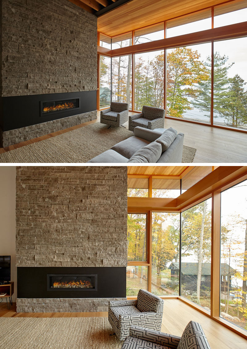 This contemporary cottage has large windows, a stone accent wall, a fireplace with a black surround, and a wood ceiling. #Cottage #Windows #WoodCeiling #Fireplace