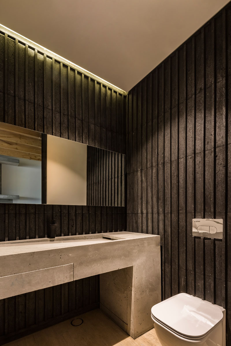 In this modern bathroom, wood detailing has been darkened, creating a strong contrast to the concrete vanity and the white ceiling. #DarkWood #ModernBathroom #ConcreteVanity