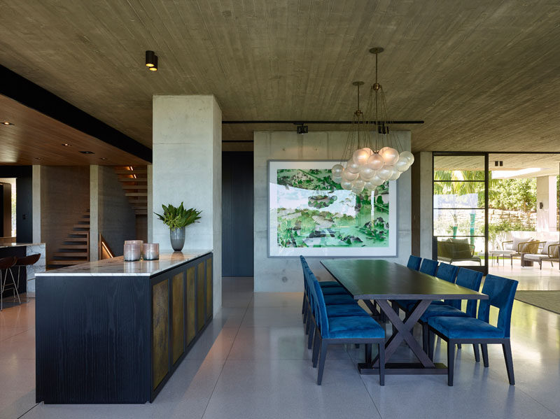 In this modern house, a pair of chandeliers hang above the large dining table, while a sideboard provides separation from the kitchen. #DiningRoom #ModernInterior