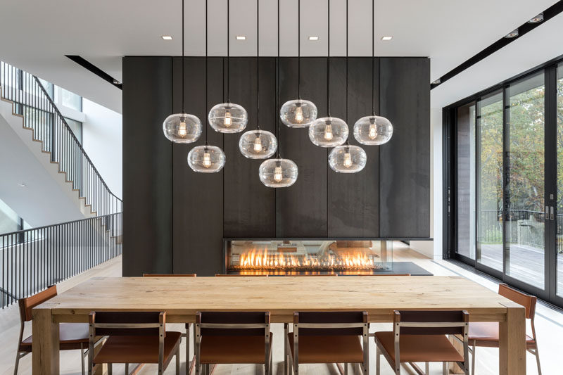 In this dining area beside a black steel fireplace, a wood dining table is positioned under a collection of pendant lights hung at different heights. #ModernDiningRoom #Fireplace