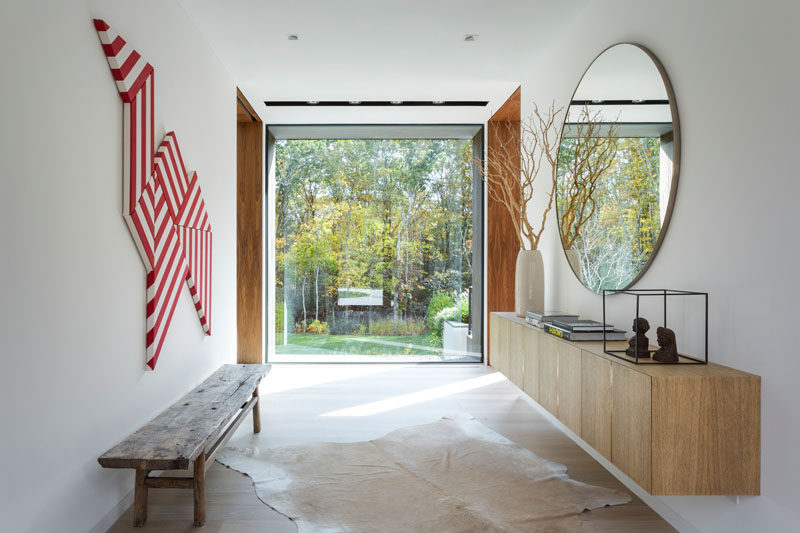 Stepping inside this modern house, the entryway has a large window that perfectly frames the trees outside. #ModernEntryway #Windows