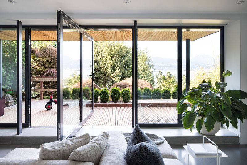 This modern family room has a large glass pivot door to create a direct connection to the outdoor garden. #PivotDoor #PivotingDoor #GlassDoor