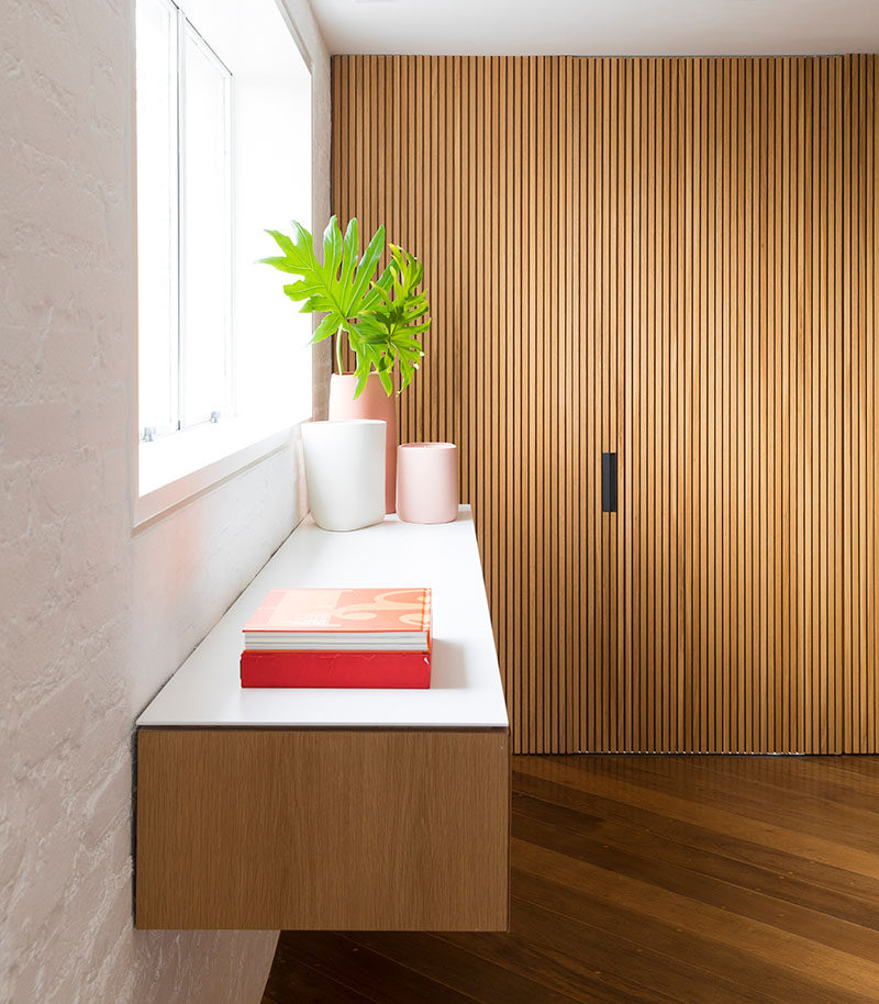 The door to the kitchen is hidden within a wood accent wall in this modern apartment. #HiddenDoor #WoodAccentWall #ModernApartment