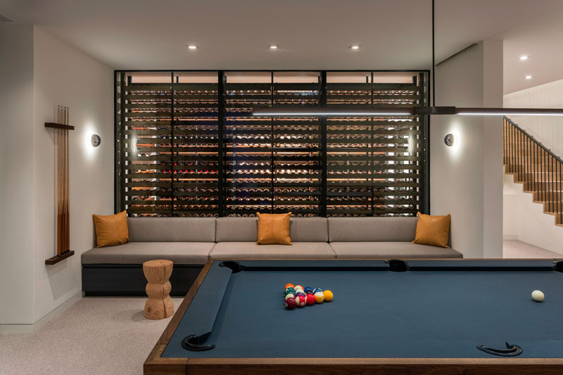This modern house has a wine room with blackened steel supports and custom walnut shelving, and is used as a back drop to a custom banquette in the game room. #WineRoom #WineCellar #GamesRoom #BanquetteSeating