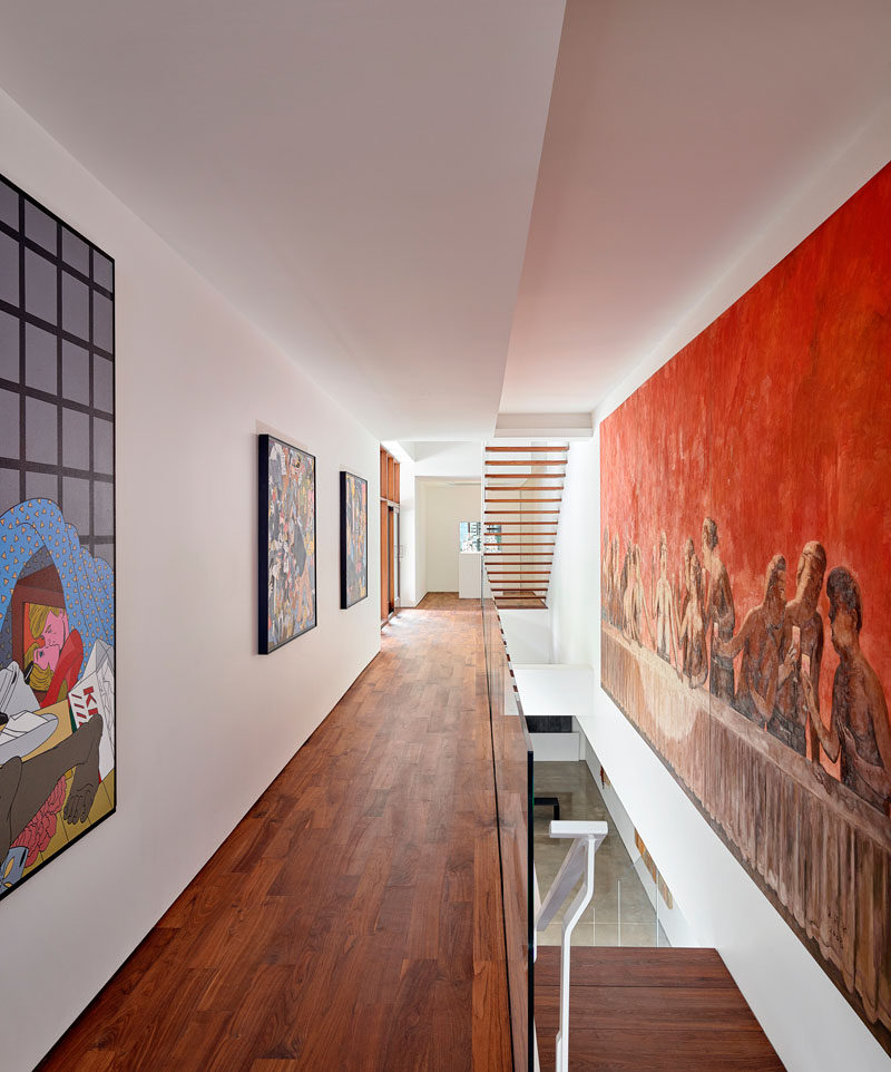 The white hallways and walls throughout this modern house are filled with art pieces. #ModernHouse #WoodFlooring #Hallways