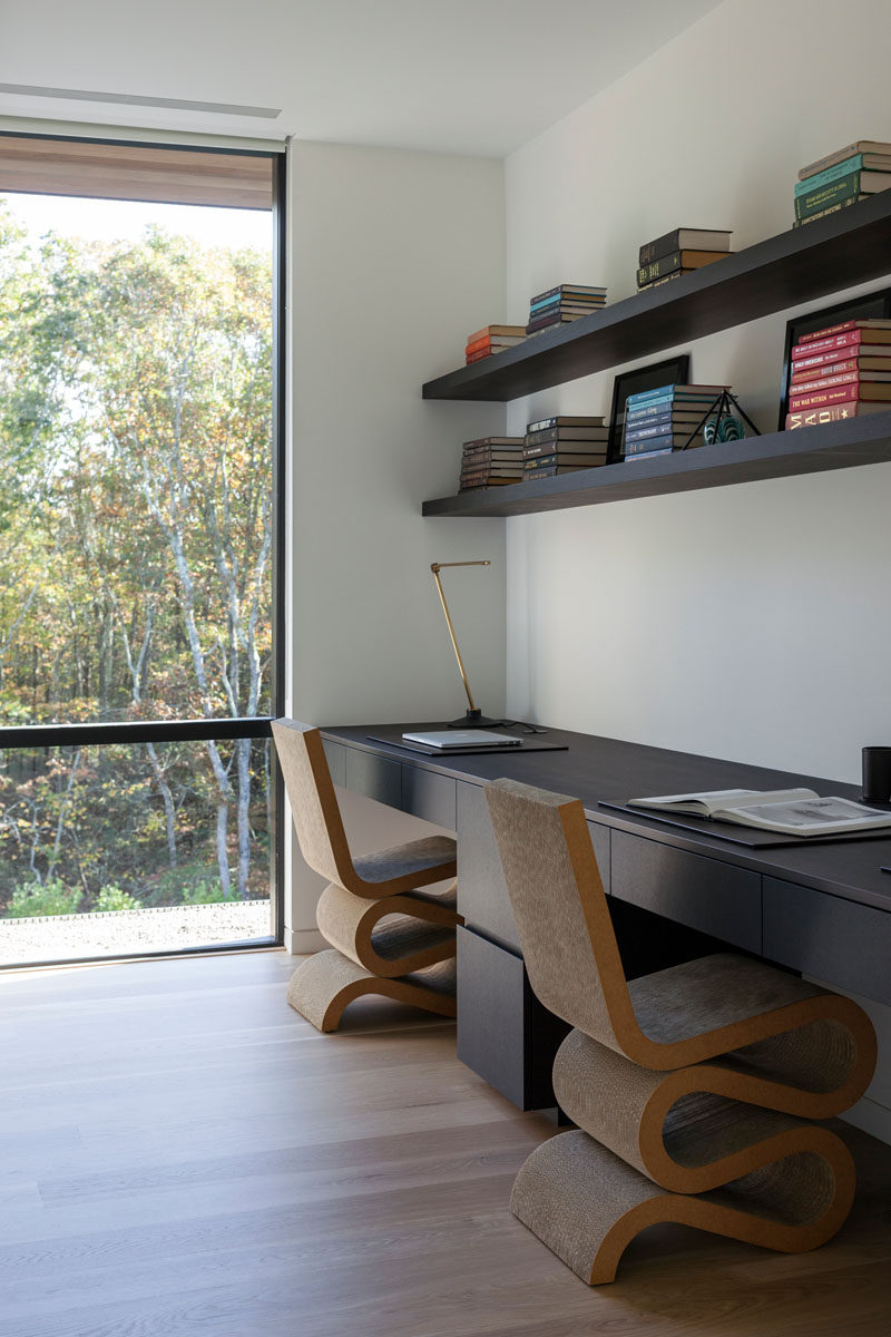 This modern home office features a built-in desk with enough room for two people, and shelving above that acts as a bookshelf. #HomeOffice #ModernHomeOffice