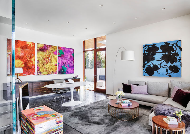 In this modern home office, there's a large sideboard that sits below colorful artwork, while a couch provides a comfortable place to relax. #ModernHomeOffice #HomeOffice