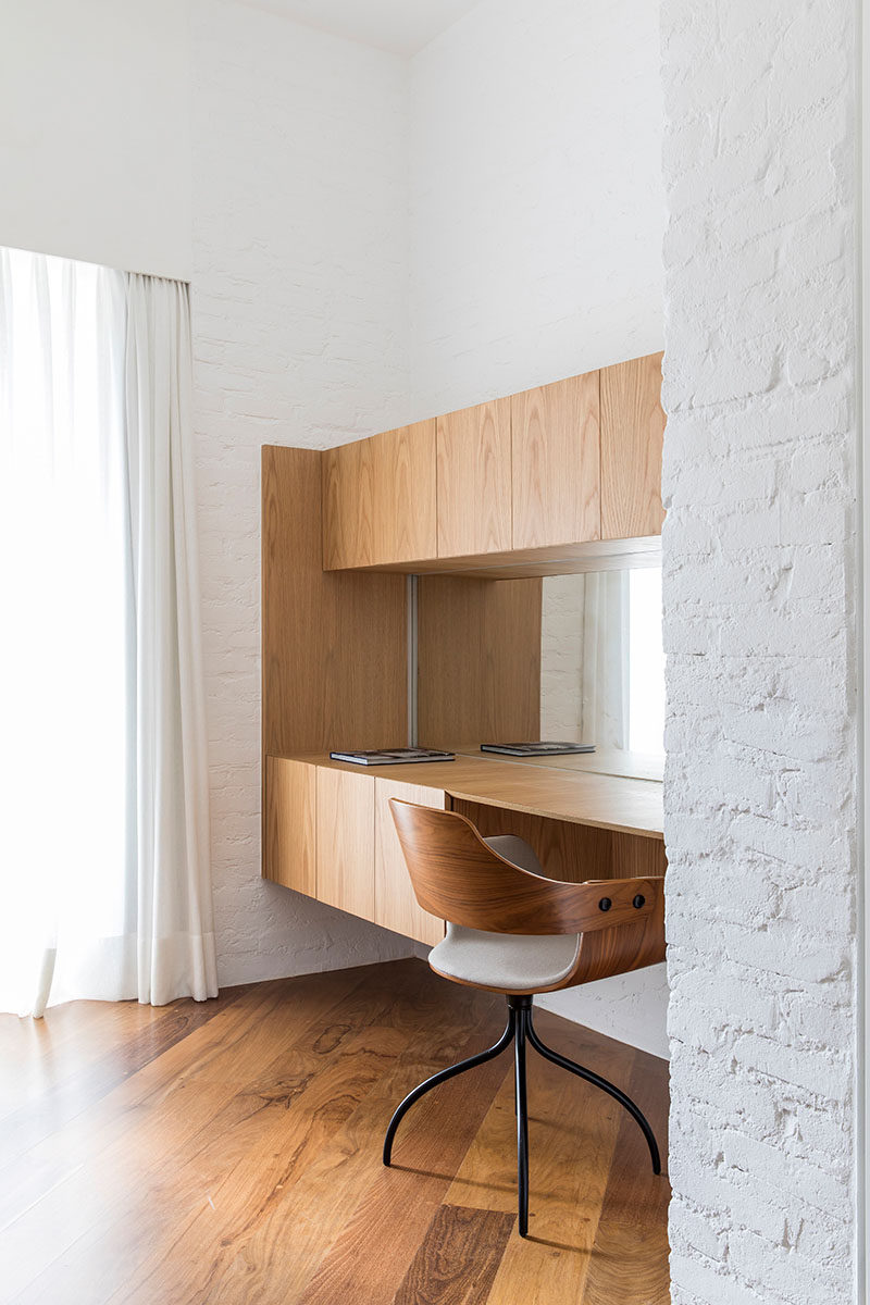 This modern master bedroom suite has a home office/vanity built into a small alcove. A mirror helps to reflect the light from the window, while the wood cabinetry provides plenty of storage. #HomeOffice #Vanity #InteriorDesign