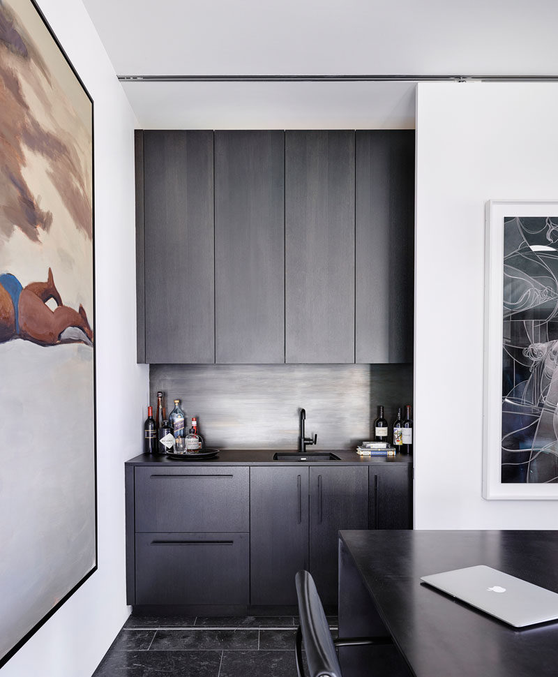 In this modern home office, there's a wet bar that's hidden behind a sliding wall. #WetBar #HiddenWetBar #HomeOffice