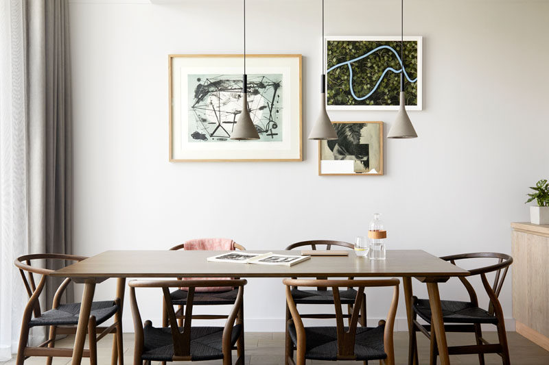 Three simple pendant lights hang above a wood dining table in this modern hotel apartment. #ModernDiningRoom #HotelRoom