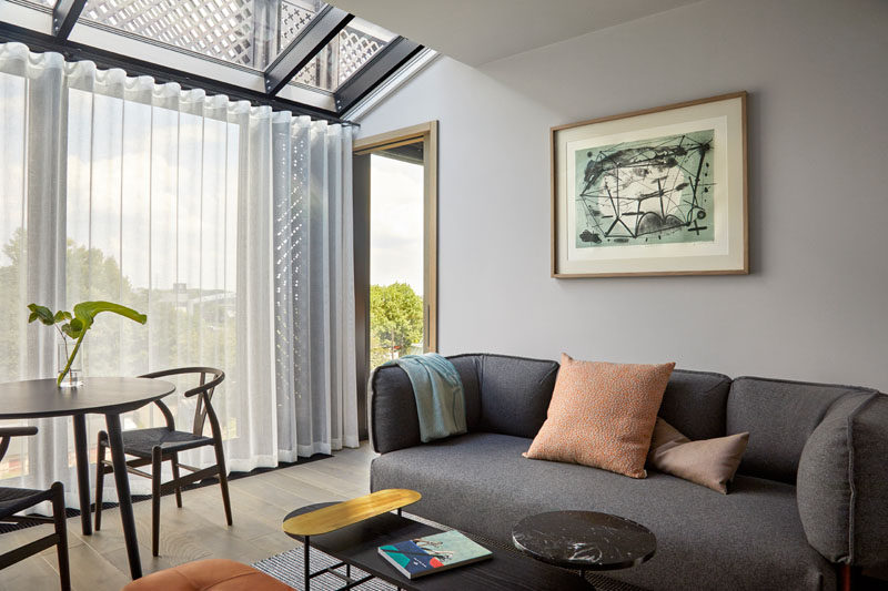 This modern hotel apartment has a simple living room with floor-to-ceiling windows and a skylight. #ModernLivingRoom #HotelRoom