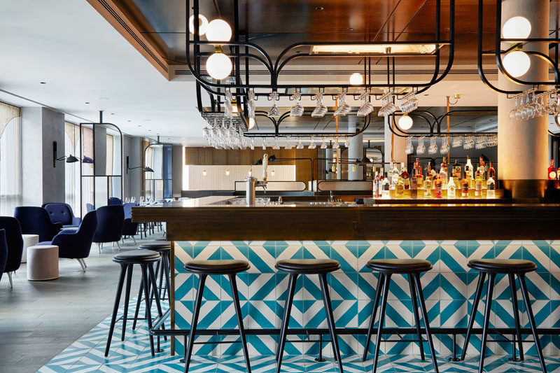 This modern hotel has a bar/restaurant with a blue and white patterned tiled bar, while hanging black racks provide a place to store glassware. #HotelBar #BarDesign