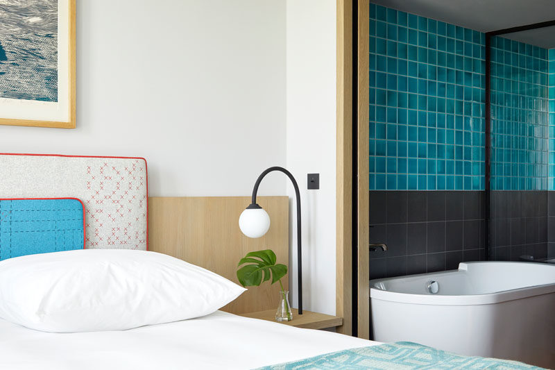 In this modern hotel room, simple furnishings have been paired with a bathroom that adds a pop of color with the use of bright blue tiles. #HotelRoom #BlueTiles #ModernBathroom