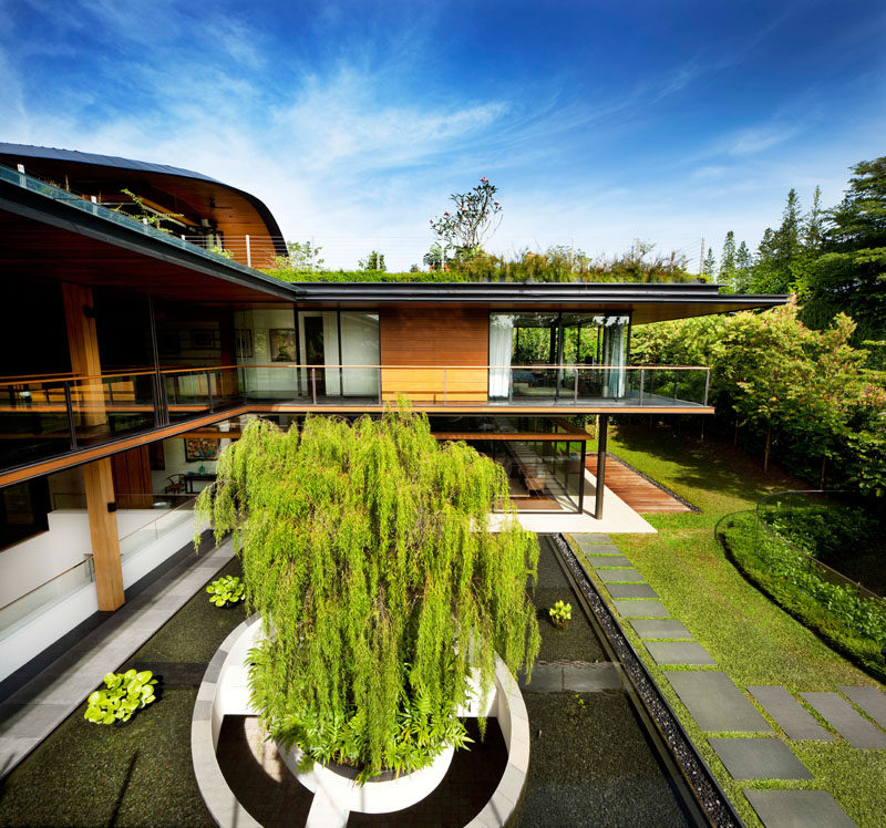 The architects designed this modern house in an L-shaped layout, allowing for the necessary privacy between two households, and at the same time providing a common courtyard and interconnected social spaces. #ModernHouse #Landscaping #Architecture #WaterFeature