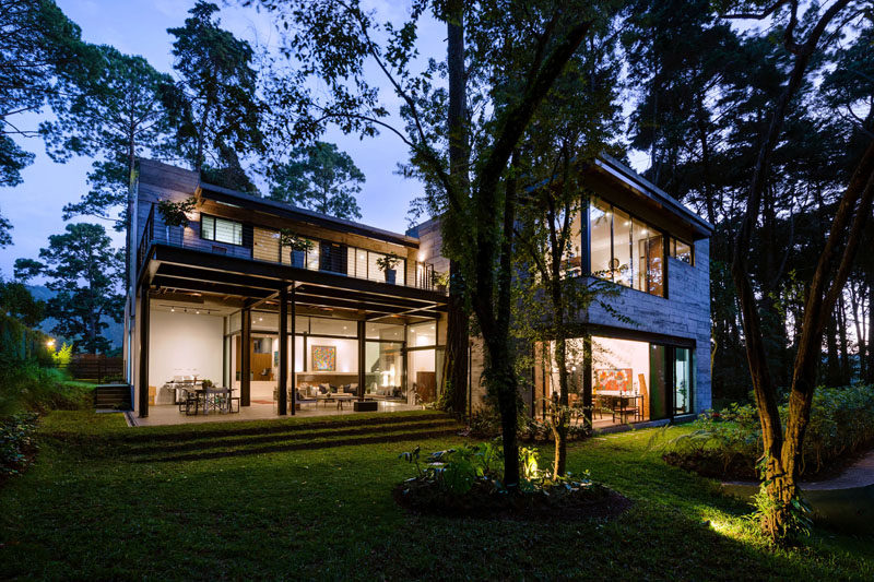 All the trees on the site of this modern house were kept and integrated in the design. In the backyard, the tall trees are highlighted are night. #ModernHouse #Trees #Landscaping