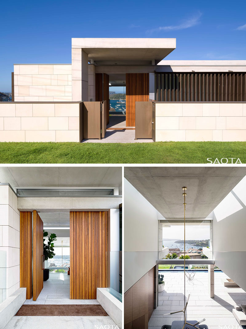 Entering the home through a pivoting wood front door, visitors step into a dramatic entrance that's emphasized by a double volume entrance space with open views right through the house to Sydney Harbour and beyond. #ModernHouse #WoodFrontDoor #PivotingFrontDoor #DoubleHeightCeiling