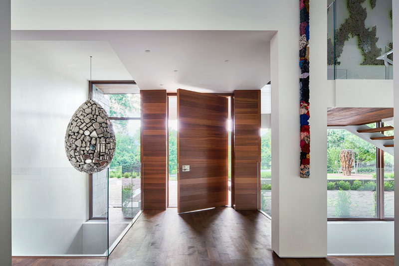 A large pivoting wood doors greets people as they arrive to this modern house, and is immediately apparent that the home is filled with art pieces. #WoodFrontDoor #PivotDoor #PivotingFrontDoor