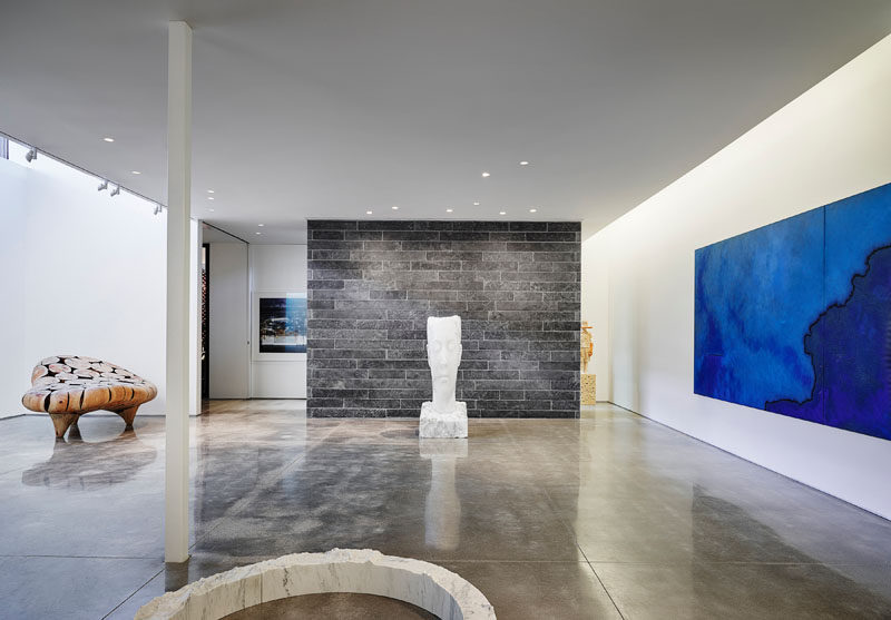 This modern home features a sub-grade gallery space that houses paintings, photography, and sculpture, spanning 20 years of collecting, with specific lighting and climate control for the preservation and display of such works. #ModernHouse #PersonalArtGallery #ArtGallery