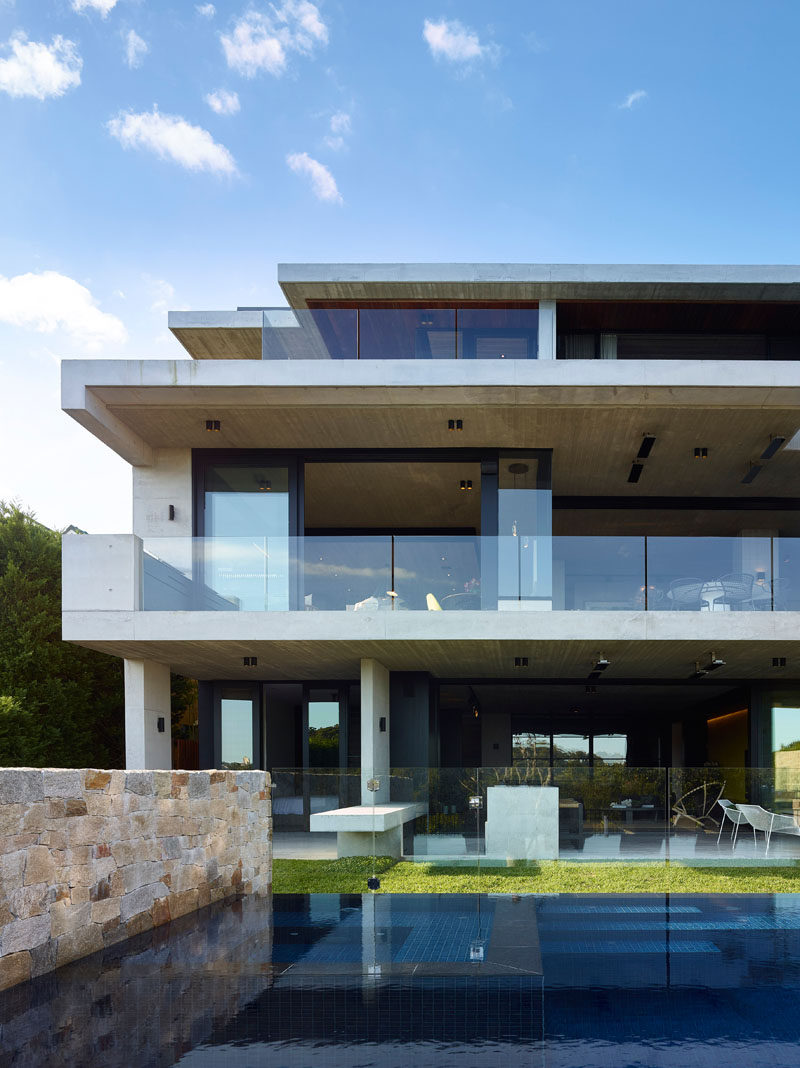The lowest level of this modern house opens up to a covered patio area and the backyard that features a swimming pool. #ModernHouse #SwimmingPool #Patio