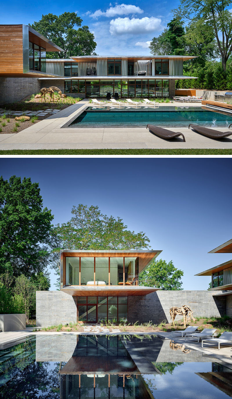 This modern house opens up to the backyard that has a swimming pool and outdoor kitchen. From this angle, you can also see the cantilevered guest suite, that's clad in cedar and aluminum. #ModernHouse #SwimmingPool #Cantilever