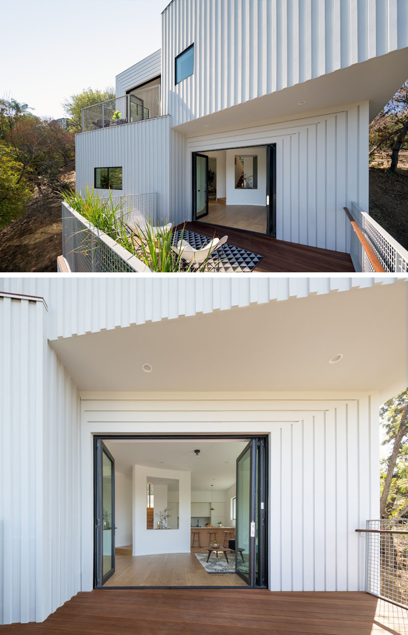 This modern four storey house has the primary living spaces (dining, kitchen, living room, and den) located on the third level. #ModernHouse #WhiteSiding #Architecture