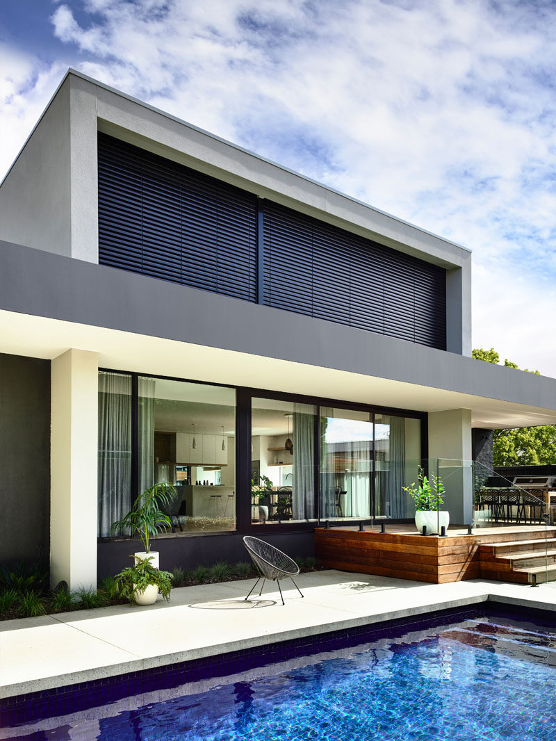 Accessed from the main social areas of this modern house, the backyard features a raised deck that overlooks the cobalt blue pool. #Deck #ModernHouse #Backyard #SwimmingPool