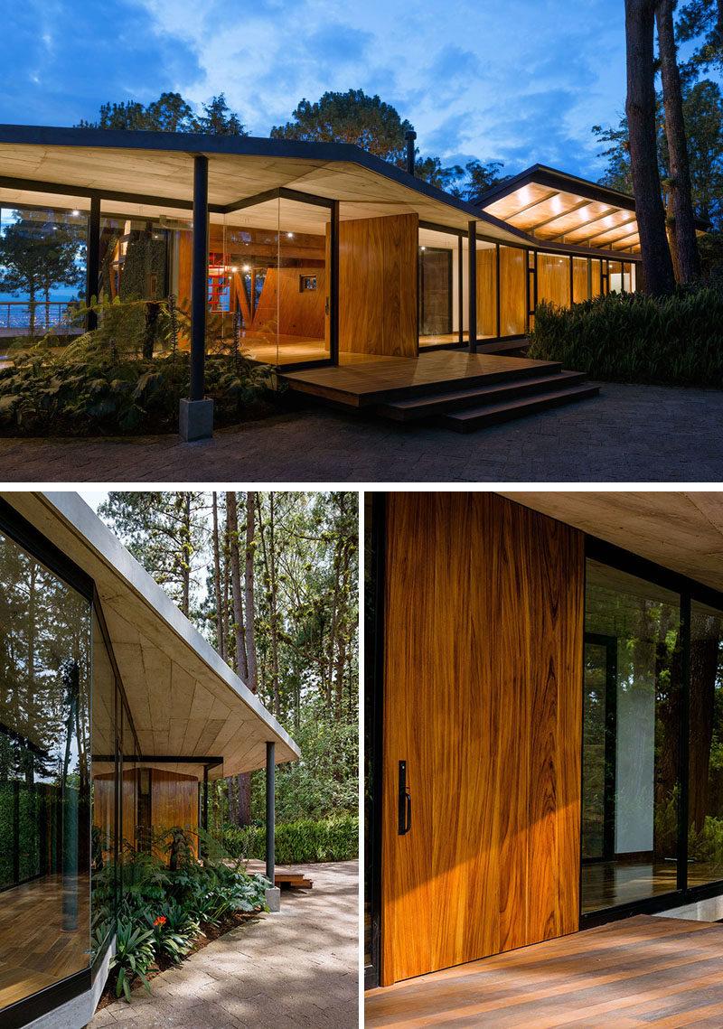 A large pivoting wood door welcomes visitors to this modern house. #FrontDoor #WoodFrontDoor #PivotingFrontDoor