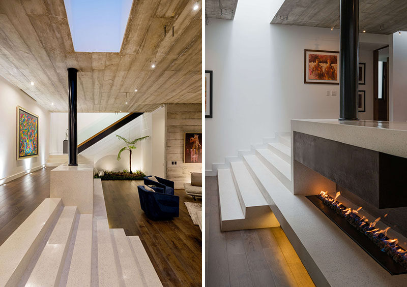 Steps, made from concrete poured in place, lead down to the living room of this modern house, that features a fireplace, whose hearth is integrated into the steps. #Fireplace #Steps #ModernHouse