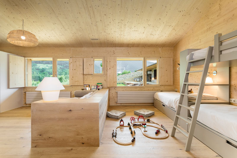In the children's bedroom, bunk beds line the wall, while a pony wall separates a small play and lounge area from the sleeping area. #KidsBedroom #BunkBeds #PonyWall