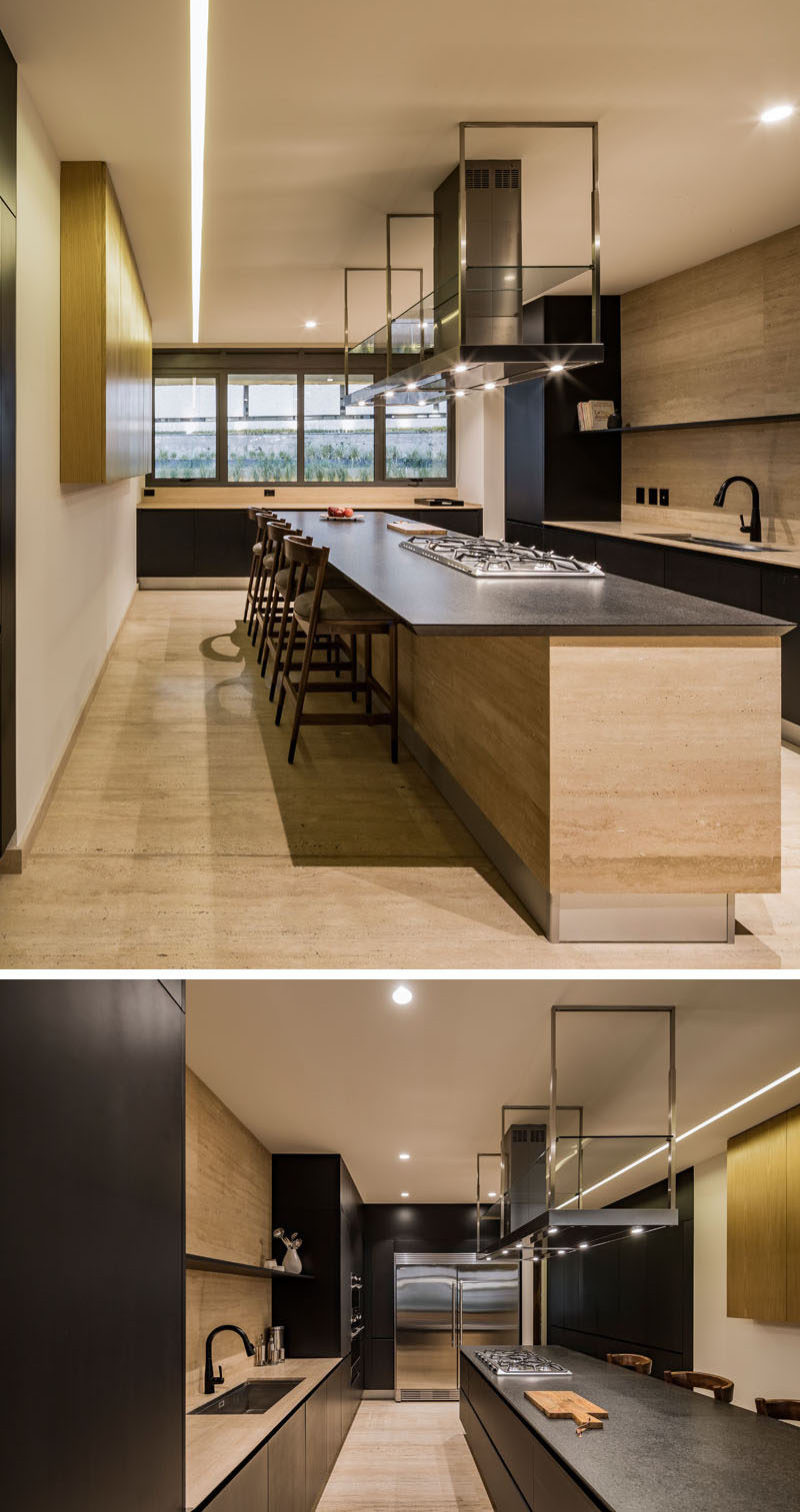 A large island is central to this modern kitchen, and the overhang provides a place for people to sit at. #KitchenDesign #LargeKitchenIsland #ModernKitchen