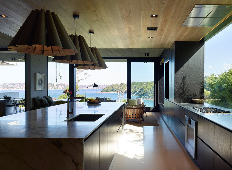 In this modern kitchen, dark wood cabinetry contrasts the light floor and ceiling, while a large picture window provides ample natural light. #KitchenDesign #ModernKitchen