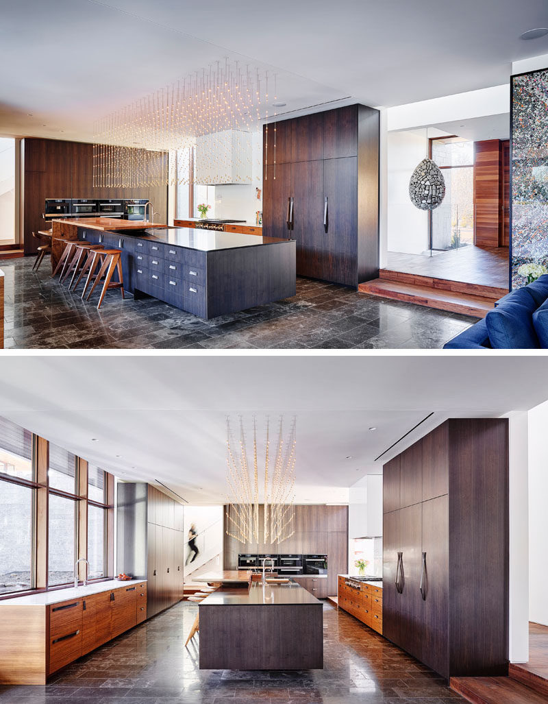In this modern kitchen, dark wood cabinetry has been paired with lighter wood accents, while a long kitchen island is positioned centrally in the space. Above the island is a decorative light installation that brightens the kitchen. #ModernKitchen #KitchenDesign