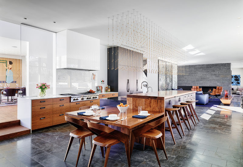 In this modern kitchen, tere's a small casual dining area attached to the end of the kitchen island, while behind the kitchen and on the other side of the hallway, is a formal dining room. #Kitchen #ModernKitchen #KitchenDesign