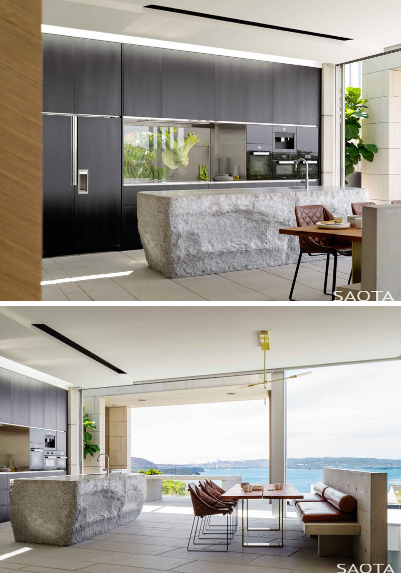 In this modern kitchen, ahand-cut grey granite kitchen island makes a statement, while dark minimalist cabinetry and glass backsplash line the wall. Also included in the same room as the kitchen, is a secondary, more casual, dining area. #ModernKitchen #KitchenDesign #Dining