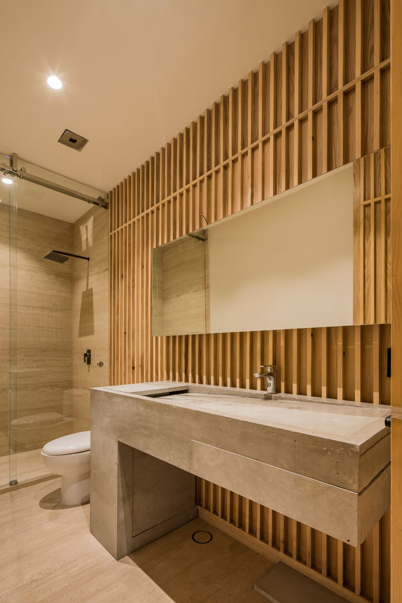 In this modern bathroom, a custom-designed concrete vanity stands out against the wood walls. #ModernBathroom #ConcreteVanity #BathroomDesign
