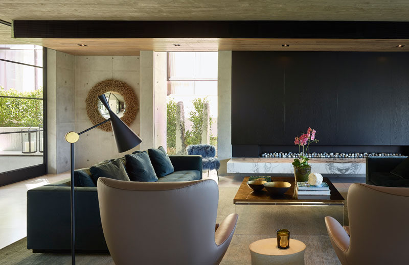 This formal living room has a long fireplace and comfortable seating that surrounds a coffee table. #LivingRoom #InteriorDesign
