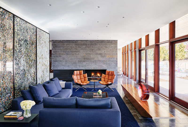 In this modern living room, large artwork becomes the backdrop for the blue couch, while floor-to-ceiling windows provide ample natural light. #ModernLivingRoom #LivingRoomLayout