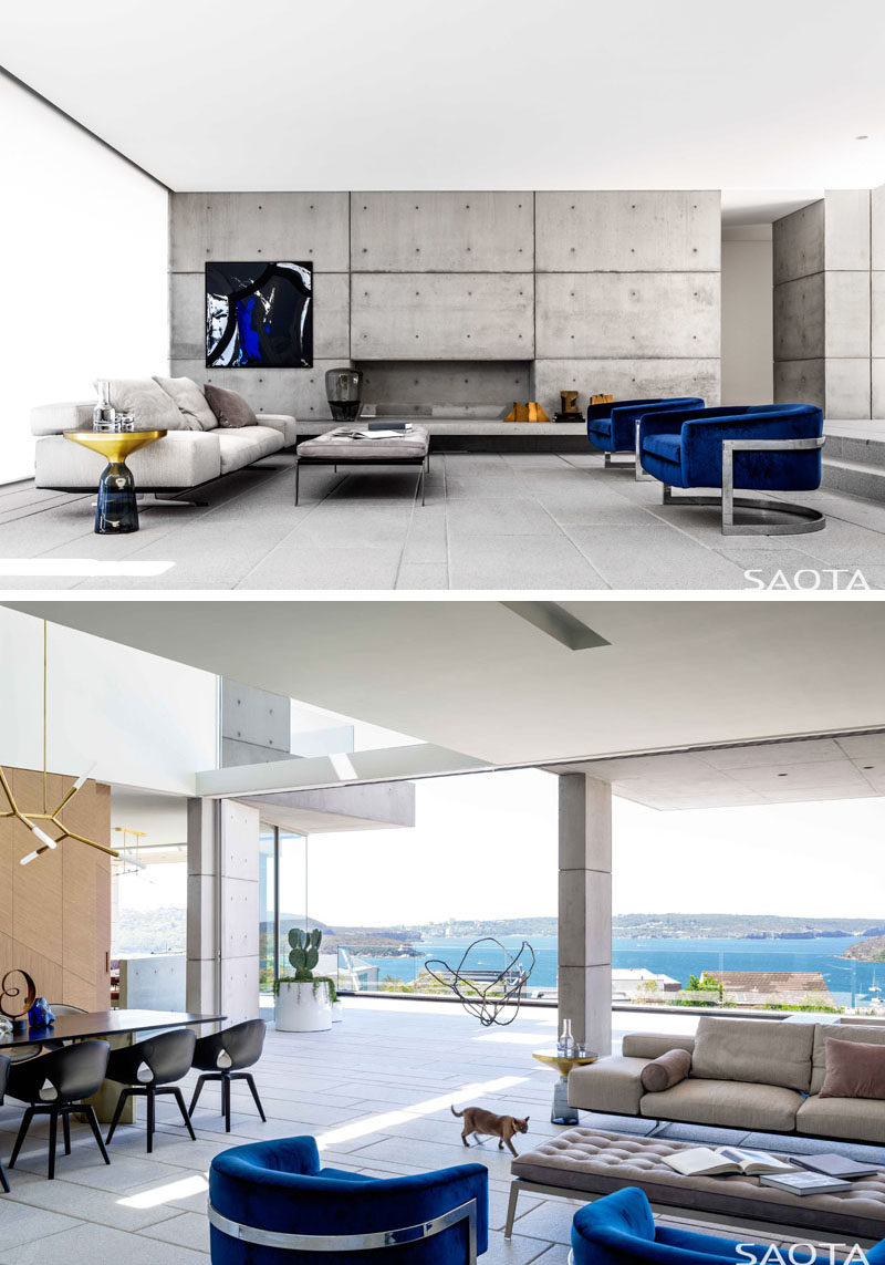 In this modern living room, neutral colors have been combined with pops of blue succeeded to create a sophisticated feeling within the home. #ModernLivingRoom #ConcreteWall #OpenPlanInterior