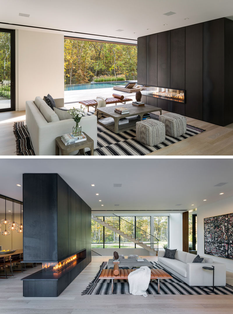 In this modern living room, the furniture is positioned to take advantage of the backyard view and the three-sided fireplace that's clad in blackened steel. #ModernLivingRoom #BlackSteelFireplace #Fireplace