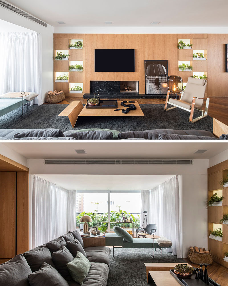 In this modern apartment, a wood accent wall with open sections for plants and displays runs the width of the apartment. #AccentWall #InteriorDesign #WoodWall #LivingRoom