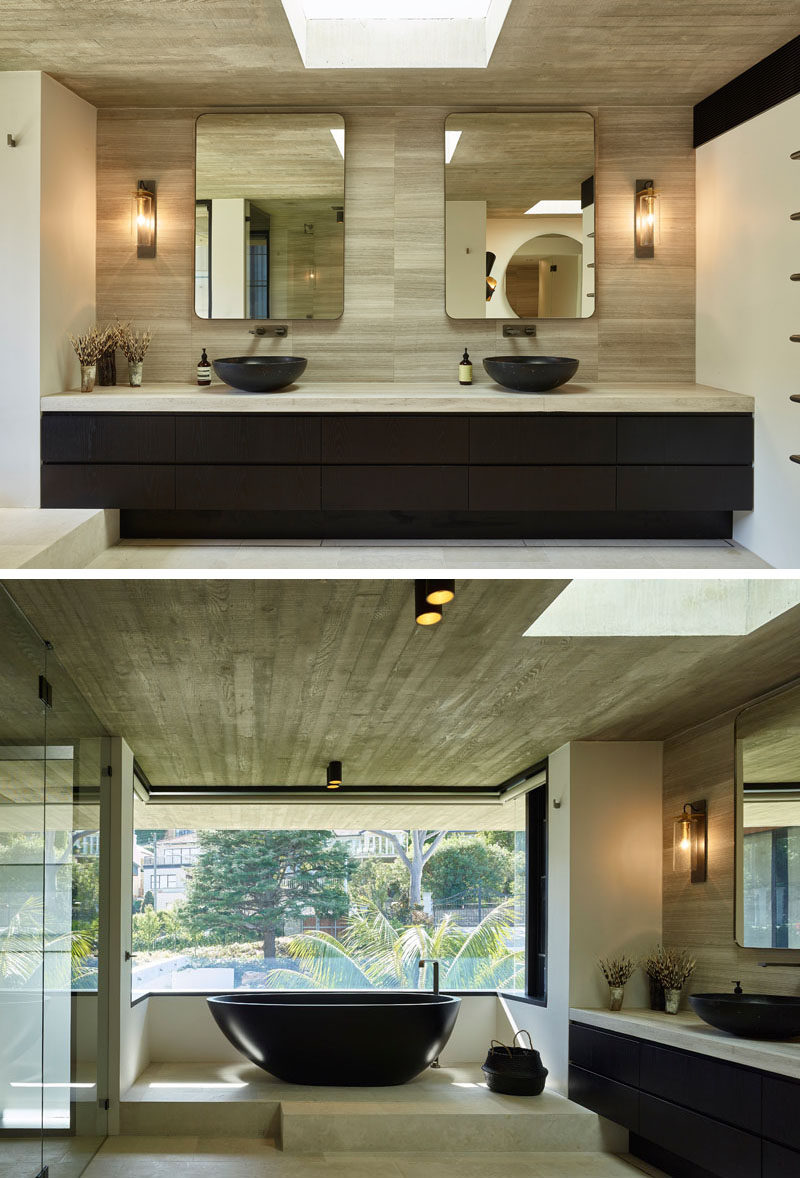 In this modern master bathroom, there's a dual sink vanity that runs the length of the wall, while a freestanding bathtub is raised up onto a platform to take advantage of the views. Blinds can be lowered when privacy is needed. #MasterBathroom #BathroomDesign