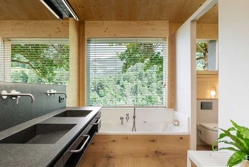In this modern master bathroom, there's a built-in bathtub located below a window, while behind a partial wall is the toilet and shower. #ModernBathroom #BuiltInBathtub