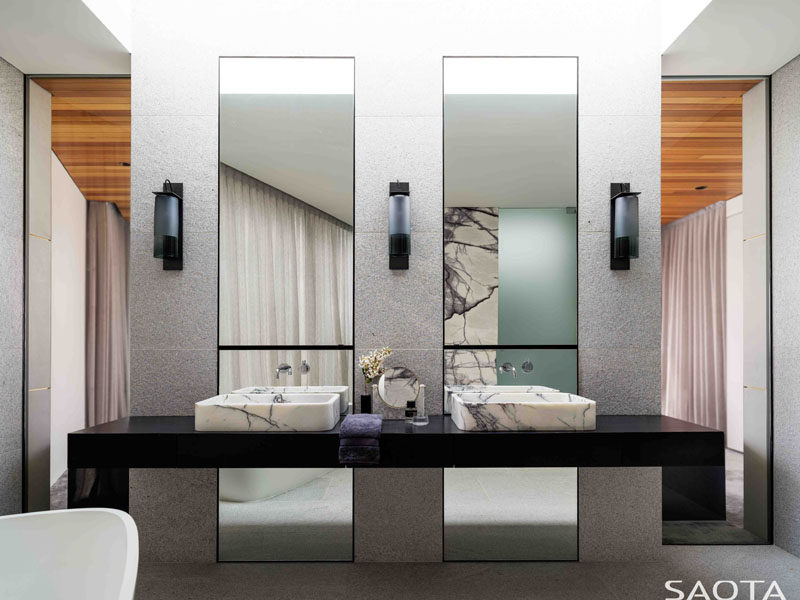 In this modern master bathroom, there's a black vanity topped with stone basins, while two tall mirrors reflect the light within the room. #MasterBathroom #EnsuiteBathroom