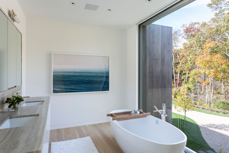 In this modern master bathroom, a freestanding bathtub is positioned in front of the large window, that adds plenty of natural light to the room. #ModernBathroom #BathroomDesign