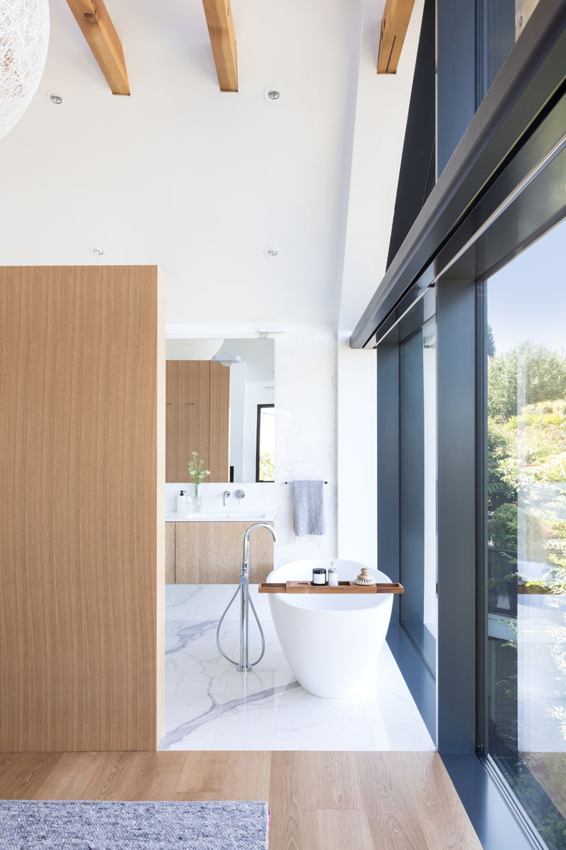 In this modern ensuite bathroom, a freestanding white bathtub is positioned in front of the windows to take advantage of the views, while further behind the wall is the vanity area, toilet and a walk-in shower. #Bathroom #ModernBathroom #FreestandingBathtub