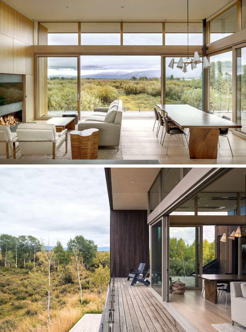 The open plan living room and dining room of this modern house, has sliding glass doors that open to a wrap-around balcony with expansive views of the landscape and mountains beyond. #ModernLivingRoom #ModernDiningRoom #SlidingGlassDoors #Balcony