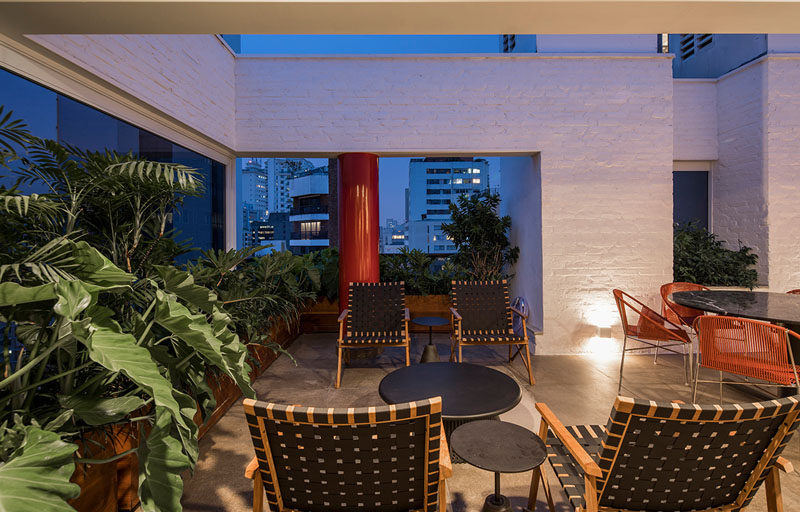 This modern apartment terrace features white bricks, concrete, wood, stone, and plenty of plants. A variety of seating areas create an outdoor living space, extending the usable space of the apartment. #ModernTerrace #ApartmentTerrace